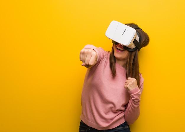 Jonge leuke vrouw draagt een virtual reality-bril die vuist toont aan voorzijde, boze uitdrukking