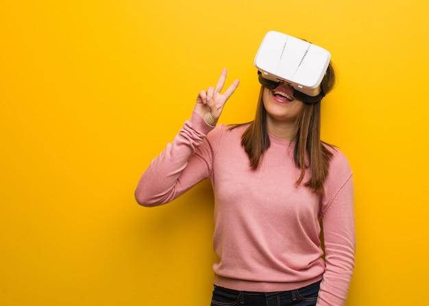 Jonge leuke vrouw draagt een virtual reality-bril leuk en gelukkig doet een gebaar van overwinning