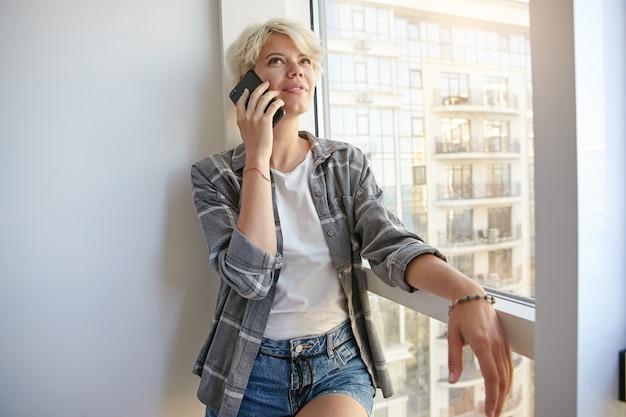 Jonge leuke vrouw met blond haar, leunend op raam, wit t-shirt, grijs geruit overhemd en spijkerbroek draagt, belt, gaat goed nieuws vertellen
