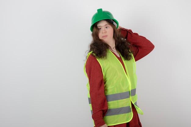 Jonge leuke vrouw met het syndroom van down die in vest staat en crashhelmen vasthoudt.