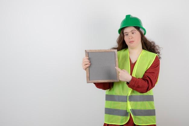 Jonge leuke vrouw met het syndroom van down die in vest staat en een frame vasthoudt.
