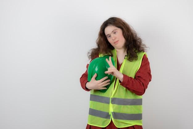 Jonge leuke vrouw met het syndroom van down die zich in vest bevindt die overwinningsteken toont.