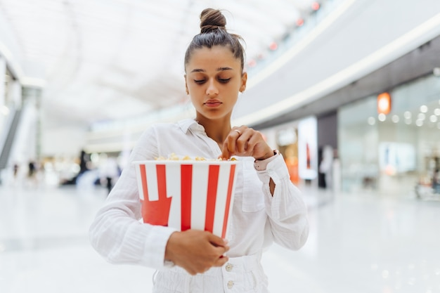 Jonge leuke vrouw met popcorn in het winkelcentrum