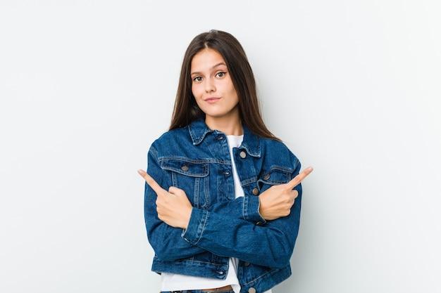 Jonge leuke vrouw wijst zijwaarts, probeert te kiezen tussen twee opties.