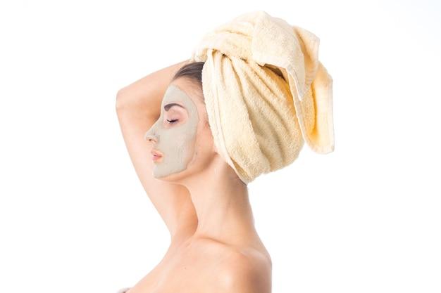 Jonge leuke vrouw zorgt voor haar huid met een reinigingsmasker op het gezicht en een handdoek op het hoofd geïsoleerd op een witte muur