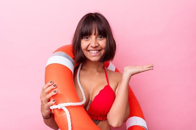Jonge leven bewaker gemengd ras vrouw geïsoleerd op roze achtergrond met een kopie ruimte op een palm en met een andere hand op de taille.