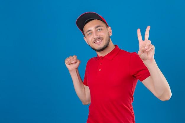 Jonge levering man dragen rode polo shirt en pet camera kijken met glimlach op gezicht verhogen vuist en overwinning teken winnaar concept tonen over geïsoleerde blauwe achtergrond