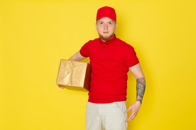 Jonge levering man in rode polo rode dop witte jeans met een doos op geel