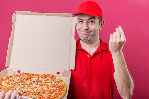Jonge levering man in rood poloshirt en pet permanent met doos verse pizza heerlijk gebaar met hand grijnst naar camera over geïsoleerde roze achtergrond