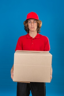 Jonge levering man in rood uniform bedrijf met kartonnen doos camera kijken met ernstig gezicht over geïsoleerde blauwe achtergrond