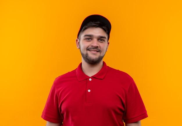 Jonge levering man in rood uniform en pet camera kijken met een glimlach op het gezicht