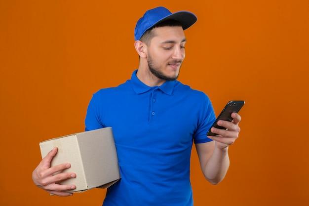 Jonge levering man met blauwe polo shirt en pet staan met kartonnen doos en kijken naar het scherm van de mobiele telefoon met glimlach op gezicht over geïsoleerde oranje achtergrond