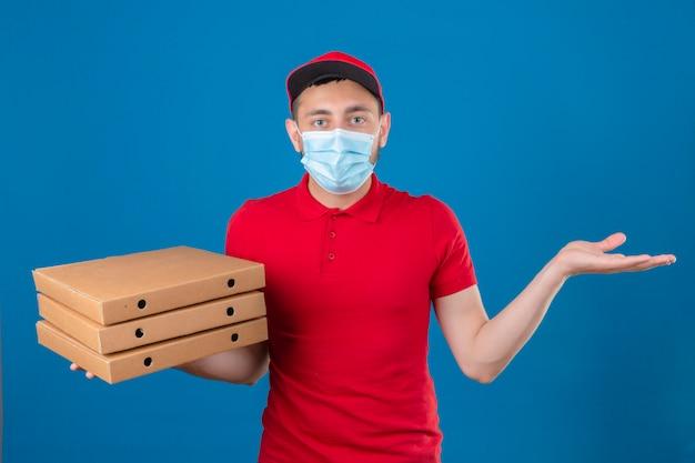 Jonge levering man met rode polo shirt en pet in beschermend medisch masker schouders ophalen en open ogen verward over geïsoleerde blauwe achtergrond