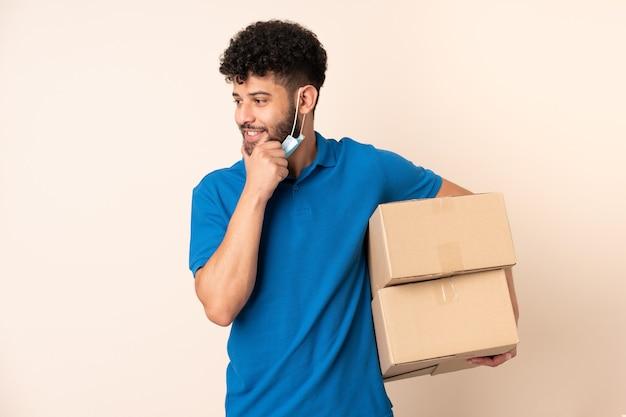 Jonge levering marokkaanse man geïsoleerd op beige achtergrond denken een idee en kijken kant