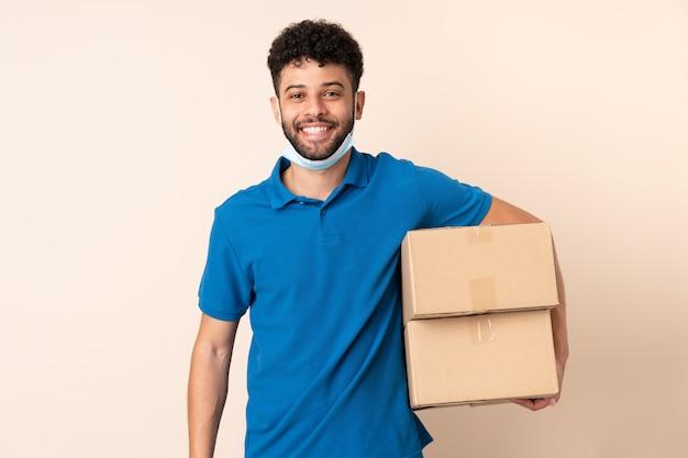 Jonge levering marokkaanse man geïsoleerd op beige achtergrond met gelukkige uitdrukking