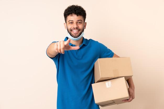 Jonge levering marokkaanse man geïsoleerd op beige muur wijst vinger naar je met een zelfverzekerde uitdrukking