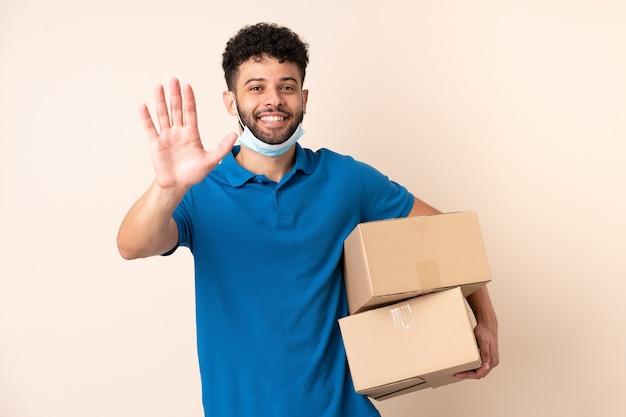 Jonge levering marokkaanse man geïsoleerd op een beige achtergrond groeten met hand met gelukkige uitdrukking