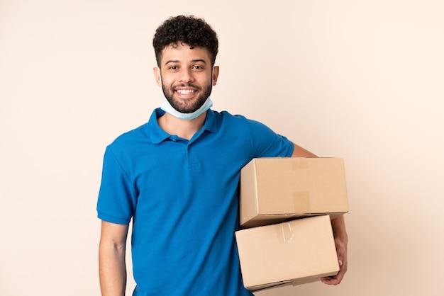 Jonge levering marokkaanse man geïsoleerd op een beige achtergrond veel glimlachen