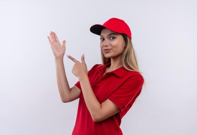 Jonge levering meisje draagt rode uniform en pet wijst naar haar hand geïsoleerd op een witte muur