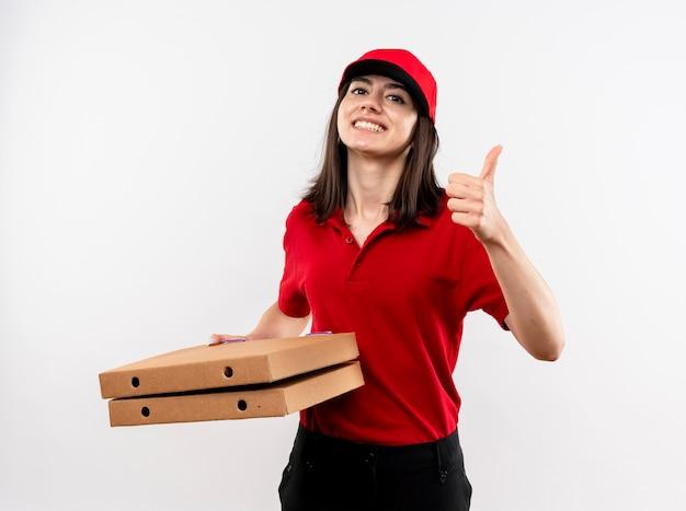 Jonge levering meisje dragen rode uniform en pet houden pizzadozen kijken camera lachend met blij gezicht duimen opdagen staande op witte achtergrond