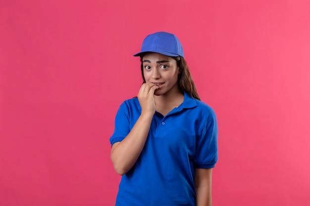 Jonge levering meisje in blauw uniform en pet camera kijken nerveus en gestrest nagels bijten permanent over roze achtergrond