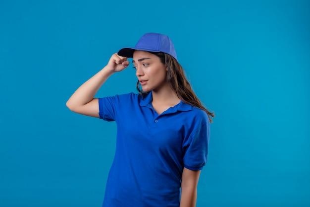 Jonge levering meisje in blauw uniform en pet clueless en verward krabben hoofd zonder antwoord staande over blauwe achtergrond