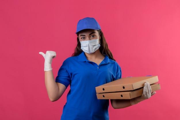 Jonge levering meisje in blauw uniform en pet dragen gezicht beschermend masker en handschoenen houden pizzadozen kijken camera glimlachend zelfverzekerd positief en gelukkig wijzend met duim naar de zijkant