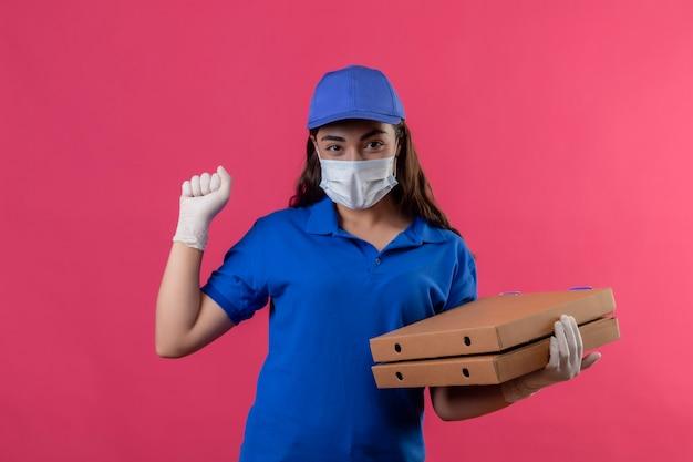 Jonge levering meisje in blauw uniform en pet dragen gezicht beschermend masker en handschoenen houden pizzadozen verhogen vuist verheugend haar succes en overwinning blij en positief glimlachend staande over