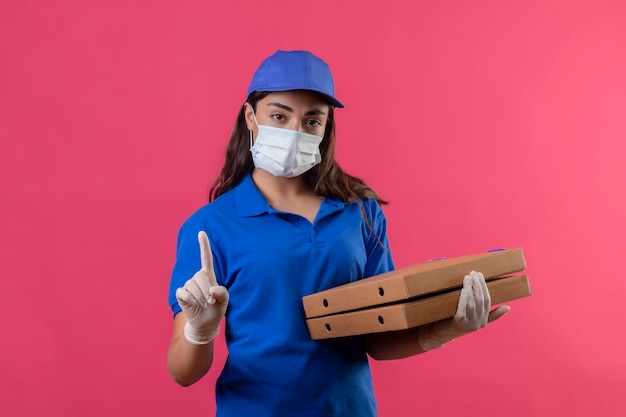Jonge levering meisje in blauw uniform en pet dragen gezicht beschermend masker en handschoenen houden pizzadozen wijzende vinger omhoog waarschuwingsgebaar camera kijken met ernstig gezicht staande over pi