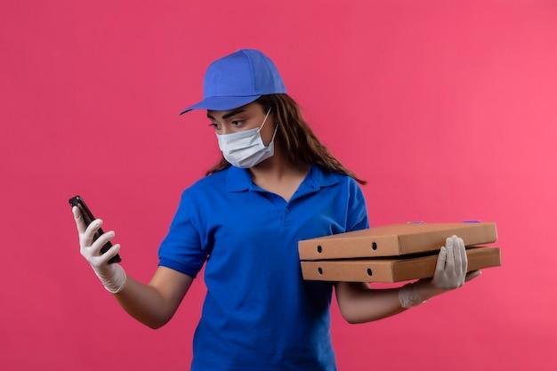 Jonge levering meisje in blauw uniform en pet dragen gezichts beschermend masker en handschoenen houden pizzadozen kijken naar scherm van haar smartphone met ernstige uitdrukking op gezicht staande over roze