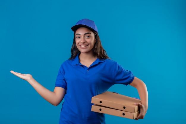 Jonge levering meisje in blauw uniform en pet houden pizzadozen presenteren met arm van de hand glimlachend vrolijk staande over blauwe achtergrond