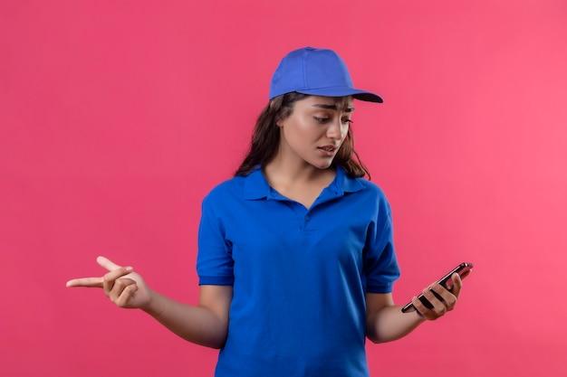 Jonge levering meisje in blauw uniform en pet van streek kijken naar scherm van haar smartphone met droevige uitdrukking op gezicht staande over roze achtergrond
