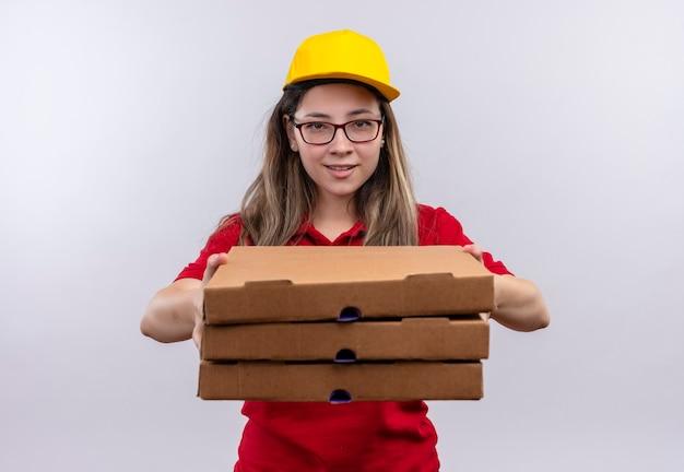 Jonge levering meisje in rood poloshirt en gele pet bedrijf stapel pizzadozen camera kijken met vriendelijke glimlach
