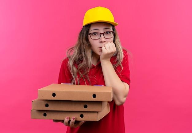 Jonge levering meisje in rood poloshirt en gele pet houden stapel pizzadozen bezorgd nagels bijten