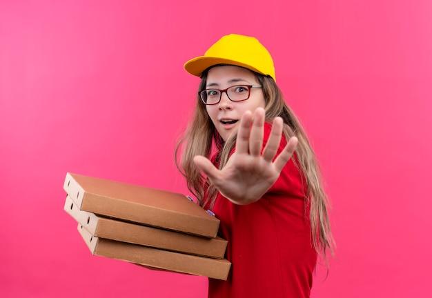 Jonge levering meisje in rood poloshirt en gele pet houden stapel pizzadozen defensie gebaar maken met open palm, bang