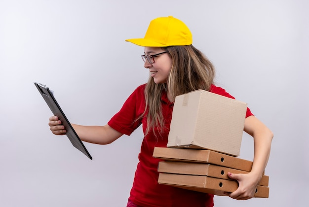 Jonge levering meisje in rood poloshirt en gele pet met stapel pizzadozen kijken naar klembord in haar andere hand op zoek verward