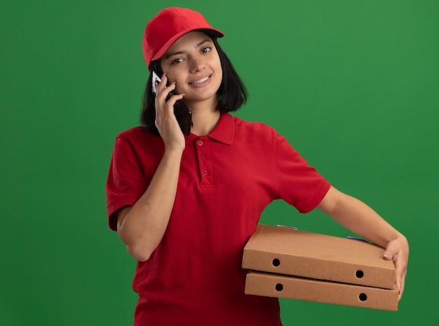 Jonge levering meisje in rood uniform en pet houden pizzadozen glimlachen terwijl praten op mobiele telefoon staande over groene muur