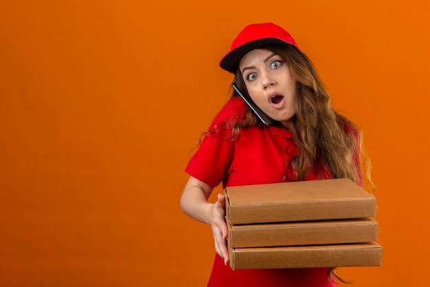 Jonge levering vrouw dragen rode polo shirt en pet geschokt staande met stapel pizzadozen met wijd geopende ogen praten op mobiele telefoon over geïsoleerde oranje achtergrond