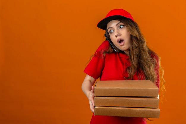 Jonge levering vrouw dragen rode poloshirt en pet geschokt staande met stapel pizzadozen met wijd geopende ogen praten op mobiele telefoon over geïsoleerde oranje achtergrond met kopie ruimte