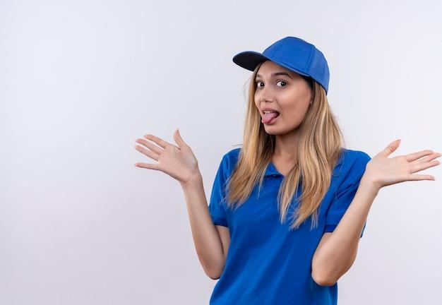 Jonge levering vrouw, gekleed in blauwe uniform en pet met tong en spreidt handen