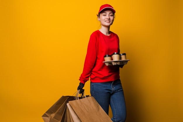 Jonge levering vrouw met koffie en papieren zakken geïsoleerd op geel