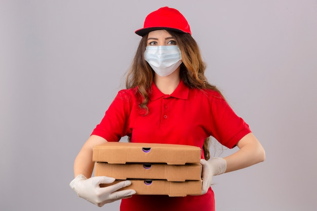 Jonge levering vrouw met krullend haar dragen rode polo shirt en pet in medische beschermend masker en handschoenen staan met pizzadozen camera kijken met glimlach op gezicht over geïsoleerde witte chtergro