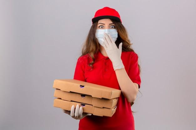 Jonge levering vrouw met krullend haar dragen rode polo shirt en pet in medische beschermend masker en handschoenen staan met pizzadozen op zoek verrast die mond bedekken met hand over geïsoleerde witte ba