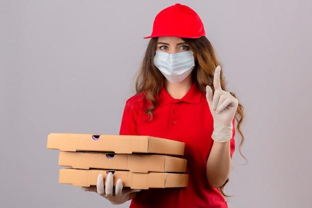 Jonge levering vrouw met krullend haar dragen rode polo shirt en pet in medische beschermend masker en handschoenen staan met pizzadozen vinger omhoog met ernstig gezicht over geïsoleerde witte chtergro