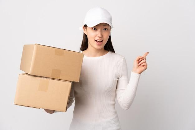Jonge leverings chinese vrouw over geïsoleerde witte muur wijzende vinger naar de kant