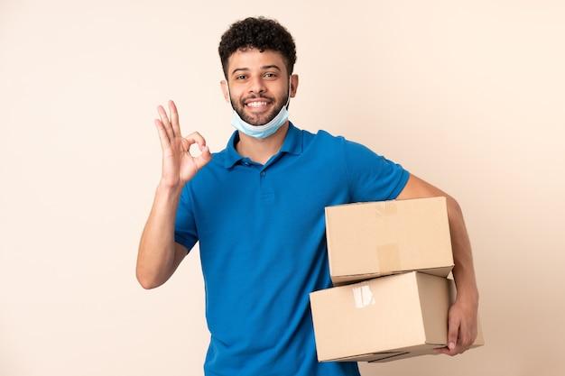 Jonge leverings marokkaanse man die op beige muur wordt geïsoleerd die ok teken met vingers toont
