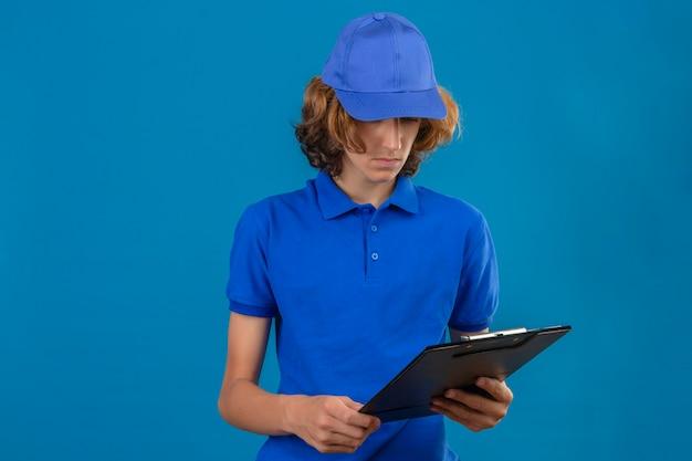 Jonge leveringsmens die blauw poloshirt en glb draagt die klembord in zijn hand bekijken met ongelukkig gezicht dat zich over geïsoleerde blauwe achtergrond bevindt