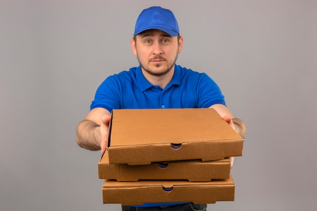 Jonge leveringsmens die blauw poloshirt en glb dragen die en stapel van pizzadozen over geïsoleerde witte achtergrond houden uitrekken