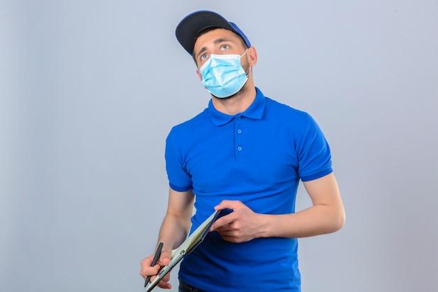 Jonge leveringsmens die blauw poloshirt en pet in beschermend medisch masker dragen die zich met klembord bevinden die omhoog denken verbaasd over geïsoleerde witte achtergrond kijken