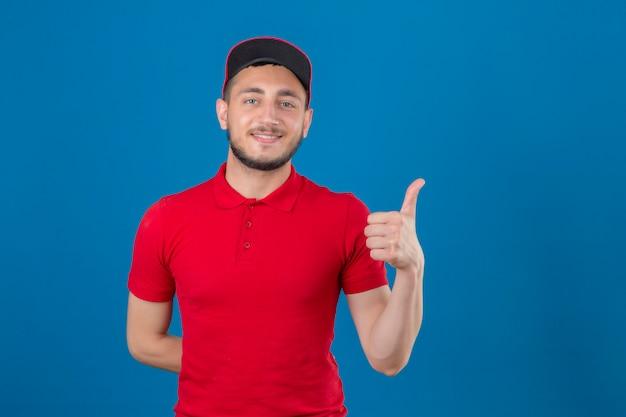 Jonge leveringsmens die rood poloshirt en glb draagt die camera met vriendschappelijke glimlach bekijkt die duim over geïsoleerde blauwe achtergrond toont